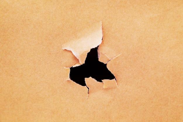Kraftpapier mit einem loch. zerrissener handwerkspapierhintergrund.