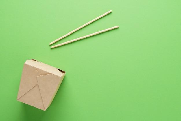 Kraftpapier- oder pappbehälter und essstäbchen auf grünem hintergrund. konzept der lebensmittellieferung. speicherplatz kopieren.