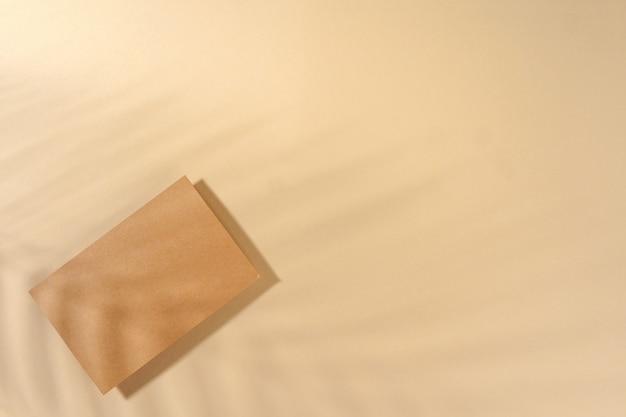 Kraftpapierbuchstabe auf draufsicht des beige hintergrundes