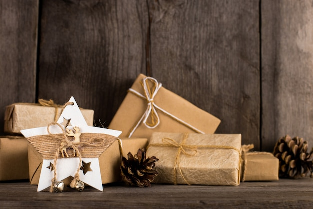 Kraftpapiergeschenke und eine weihnachtssterndekoration auf einem alten hölzernen bücherregal.