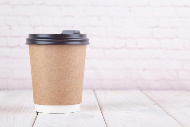 Kraftpapierkaffeetassen auf einer weißen tabelle nahe hellem wandhintergrund