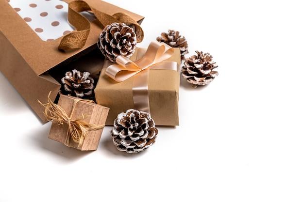Kraftpapiertüte mit geschenken und tannenzapfen auf weißer oberfläche