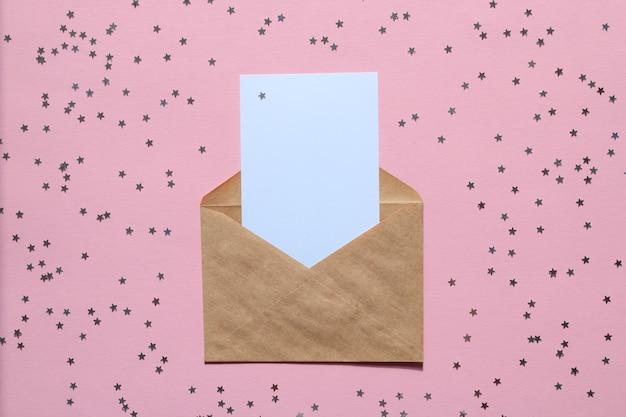 Kraftpapierumschlag brief mit leerem weißen kartenmodell auf rosa hintergrund mit konfetti-sternen.