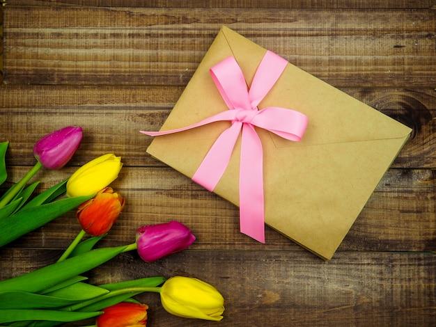 Kraftpapierumschlag gebunden mit einem rosa band auf hölzernem hintergrund mit tulpen