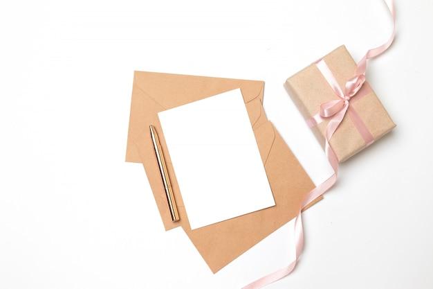 Kraftpapierumschlag mit leerem blatt und überraschungsgeschenkbox