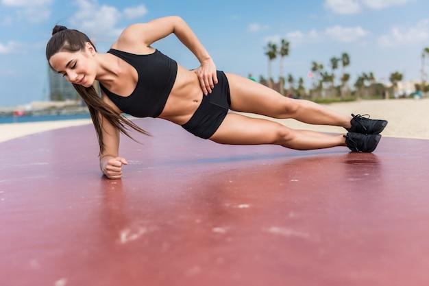 Krafttraining der fitnessfrau ihre körperkernmuskeln mit yoga-pose. athlet, der auf einem arm plankiert, der seitenplanke und hüftlift tut.
