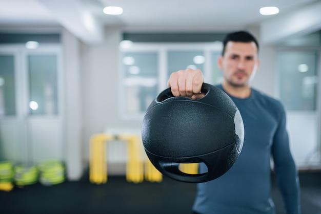 Krafttraining konzept. bemannen sie das halten des doppelgriffmedizinballs, fokus auf dem vordergrund, auf dem ball.