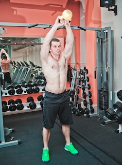 Kraftvoll und stark. athletischer mann mit nacktem oberkörper, der übungen mit kettlebell im fitnessstudio macht