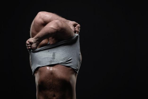 Kraftvoller muskulöser mann zieht sein t-shirt aus
