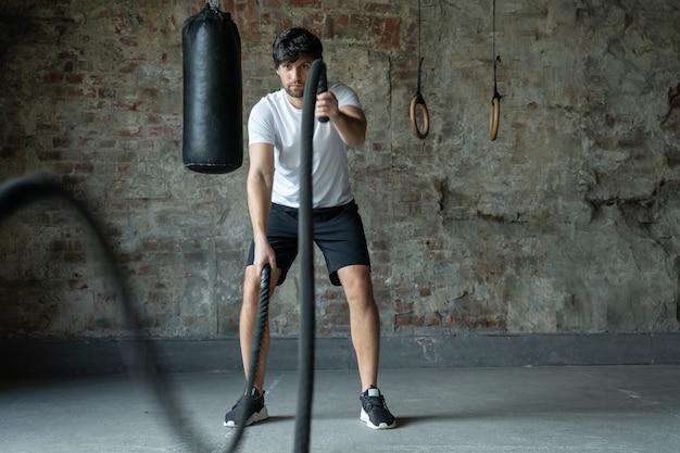 Kraftvolles manntraining mit seil im funktionstraining fitness-fitness-crossfit-seile trainieren während des athletentrainings im workout-fitnessstudio