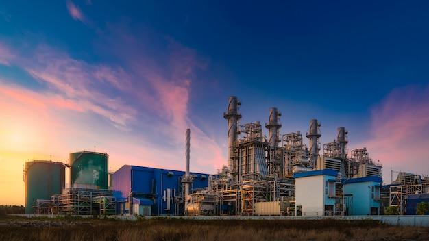 Kraftwerk für industriegebiet in der dämmerung, erdgas-kombikreislauf, kraftwerk und turbinengenerator. energiekraftwerk der industriellen raffinerie öl und gas in der dämmerung zur stromversorgung