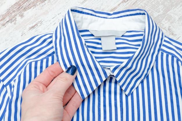 Kragen des gestreiften weiß-blauen hemdes in einer weiblichen hand. nahansicht. modisch.