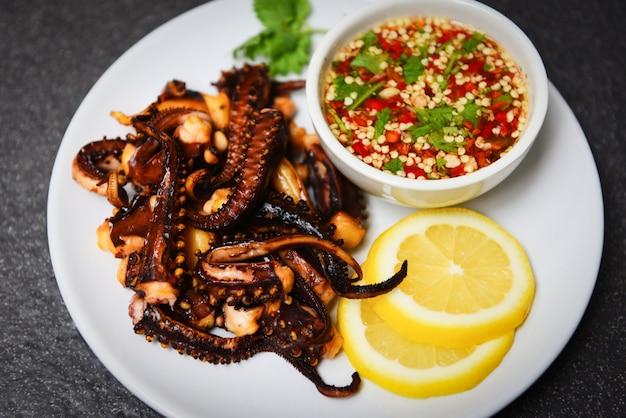 Krakensalat mit zitronenkräutern und -gewürzen auf weißer platte. ssquid grillte scharfe und würzige paprikasoße des aperitiflebensmittels.