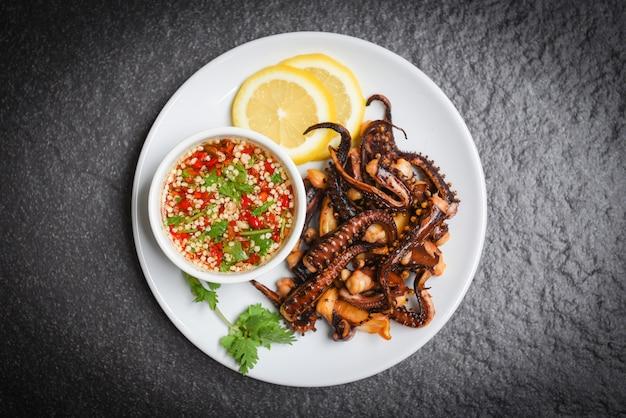 Krakensalat mit zitronenkräutern und -gewürzen auf weißer platte