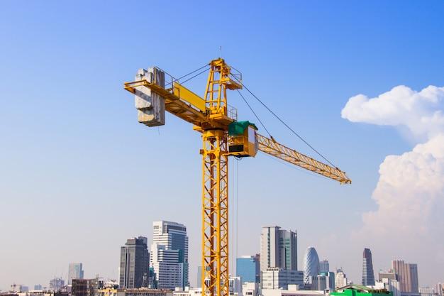 Kran wird beim bau von hochhäusern für werkzeug der großindustrie unter dem blauen himmel verwendet.