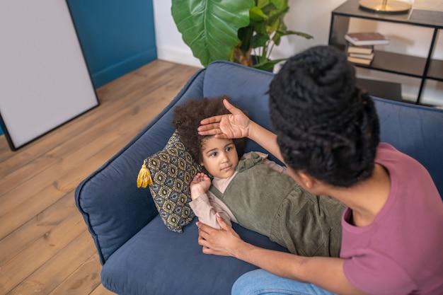 Krank, fieber. dunkelhäutiges trauriges kleines mädchen, das zu hause auf dem sofa liegt und die mutter neben ihrer hand sitzt und die stirn berührt