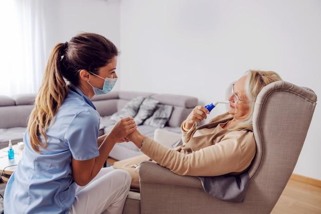 Kranke ältere frau, die im stuhl zu hause sitzt und sauerstoff vom atemschutzgerät einatmet.