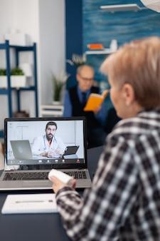 Kranke ältere frau im gespräch mit jungem arzt während der fernsprechstunde talking