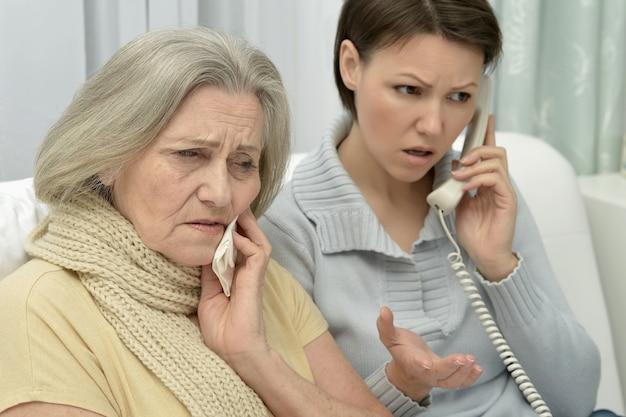Kranke ältere frau mit fürsorglicher besorgter tochter mit telefon