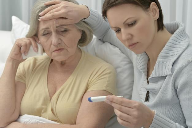 Kranke ältere frau mit fürsorglicher tochter mit thermometer