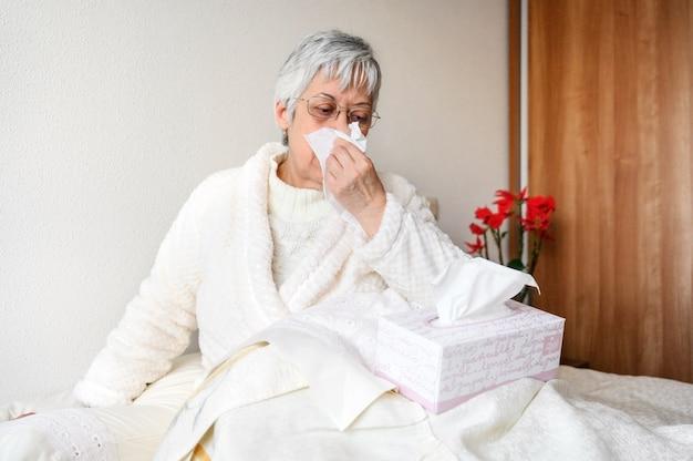 Kranke ältere frau mit papiertuch, das seine nase zu hause putzt.