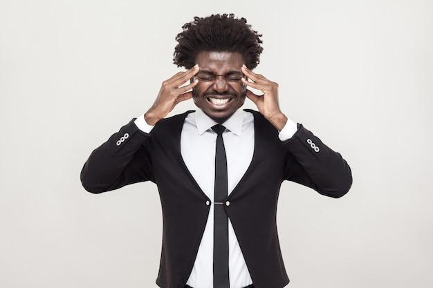 Kranke afro-mann haben kopfschmerzen und migräne. studioaufnahme, grauer hintergrund