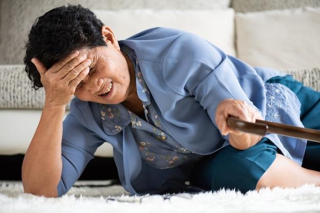 Kranke asiatische alte frau mit kopfschmerzen, die auf dem boden liegen