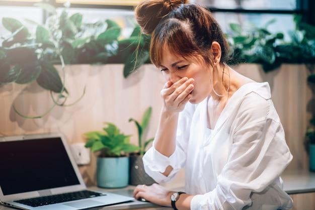 Kranke asiatische frau hat fieber und grippesymptome, kältegefühl und niesen im büro - gesundheitskonzept