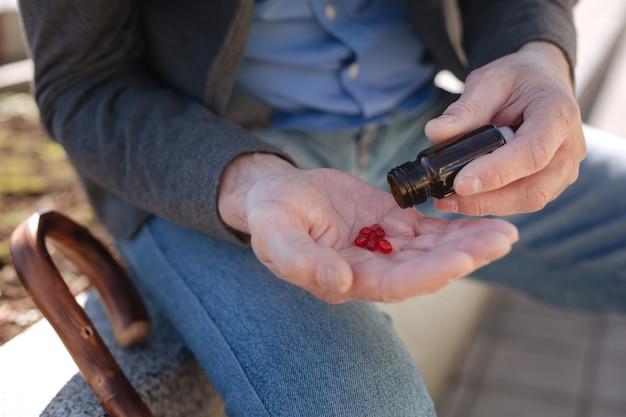 Kranke, enttäuschte rentner, die tabletten einnehmen, während sie sich entspannen und spazieren gehen
