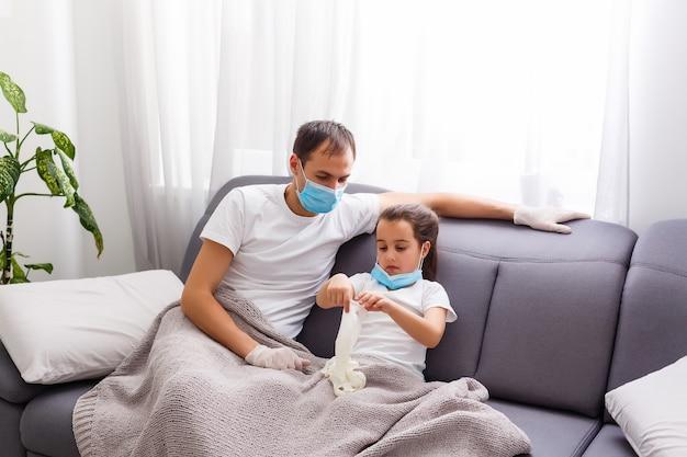Kranke familie sitzt zu hause auf dem sofa