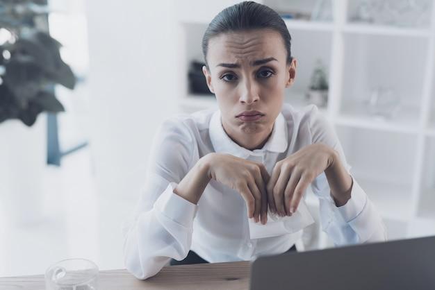 Kranke frau, die an ihrem arbeitsplatz im büro sitzt