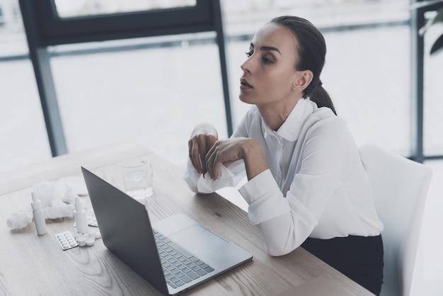 Kranke frau, die an ihrem arbeitsplatz im büro sitzt.