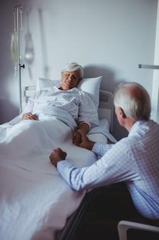 Kranke frau, die auf bett schläft, während besorgter mann neben ihrem bett sitzt