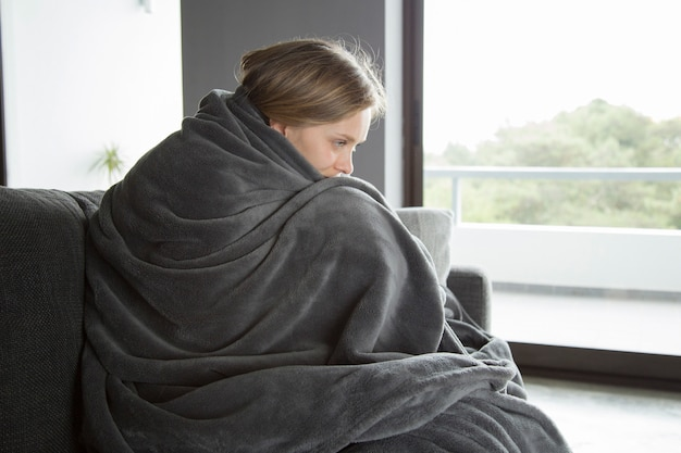 Kranke frau, die auf sofa sitzt, ihre knie umarmend und denken