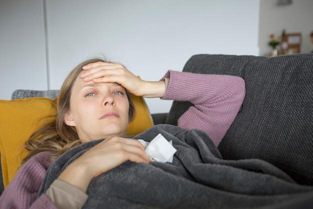 Kranke frau, die eine hand auf kopf, serviette in einer anderen hält