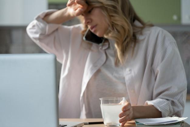 Kranke frau, die funkelndes wasserglas mit auflösender sprudelnder aspirinpille hält, die medikamente nimmt