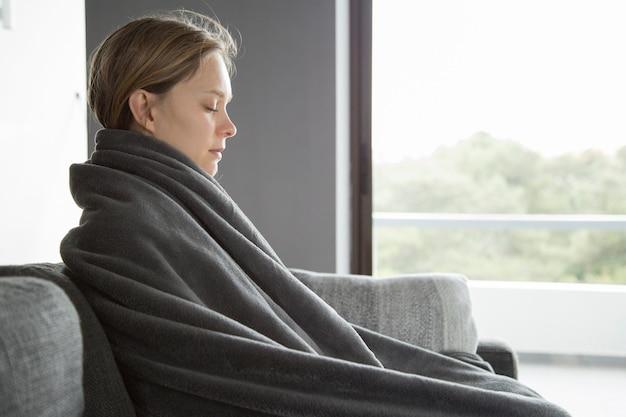 Kranke frau, die ihre augen geschlossen hält und zu hause meditiert