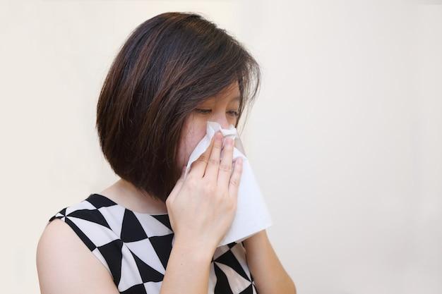 Kranke frau, die im gewebe niest