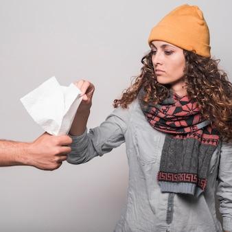 Kranke frau, die seidenpapier von der hand des mannes gegen grauen hintergrund nimmt