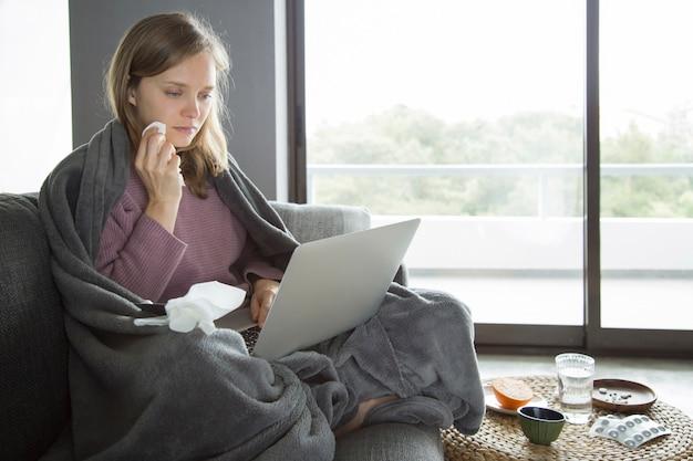 Kranke frau, die serviette am gesicht, laptop auf knien halten nimmt