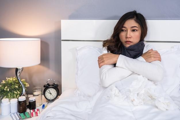 Kranke frau, die sich im bett kalt fühlt