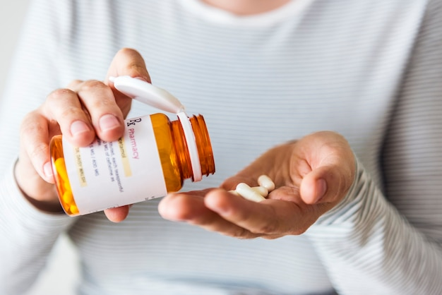 Kranke frau, die tabletten aus der flasche nimmt
