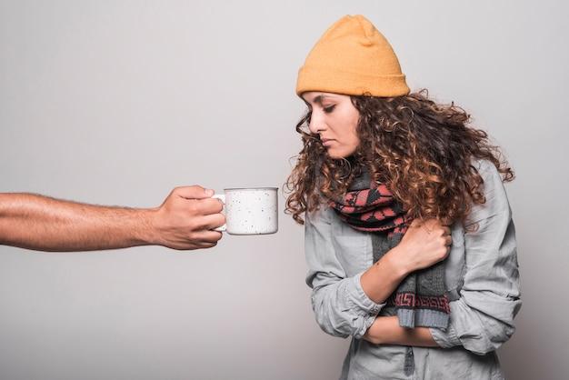 Kranke frau, die unter dem kalten schauen in der kaffeetasse hält vom mann leidet