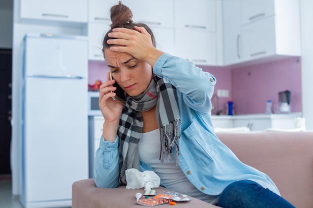 Kranke frau, die unter starken kopfschmerzen während der grippe leidet und hausarzt nach hause ruft. kältebehandlung zu hause.