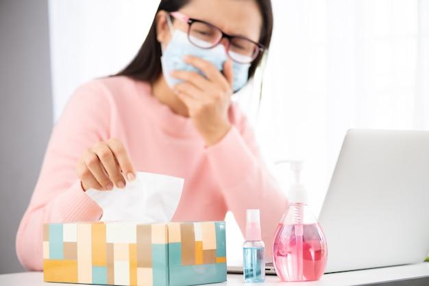 Kranke frau, die weißes seidenpapier beim husten nimmt. desinfektionsgel, medizinische gesichtsmaske
