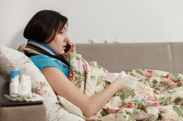 Kranke frau, die zu hause im bett liegt und telefoniert.