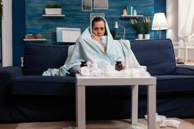Kranke frau, die zu hause in eine decke auf dem sofa gehüllt ist, fühlt sich kalt krank an einer viruskrankheit.