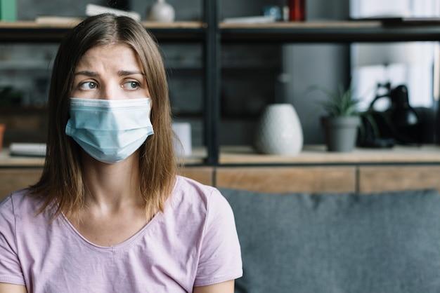 Kranke frau, die zu hause schutzmaske trägt