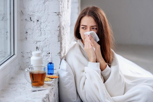 Kranke frau erkältet, sich krank fühlend und beim papiertuch niesend