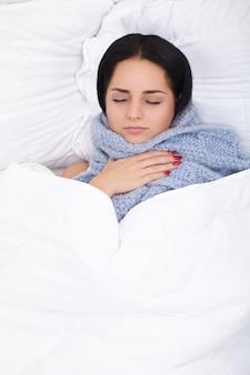Kranke frau. grippe. mädchen mit dem kalten lügen unter einer decke, die ein gewebe hält